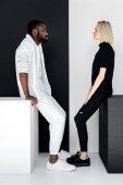 boční pohled na multikulturní pár sedí na kostky černé a bílé, jin jang koncept