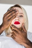Fotografie cropped image of african american boyfriend touching blonde girlfriend face with hands