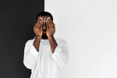 stylish african american man in white clothes closing eyes with hands
