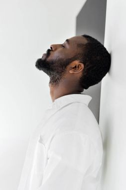 side view of handsome stylish african american man in white clothes leaning on wall with closed eyes