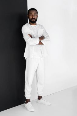 stylish african american man standing with crossed arms and looking at camera