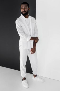 handsome stylish african american man in white clothes looking away