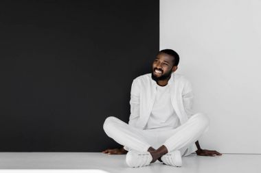 smiling stylish african american man sitting on floor near black and white wall