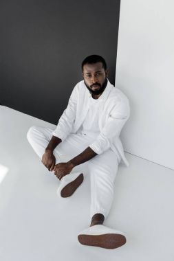 high angle view of handsome stylish african american man sitting on floor near black and white wall
