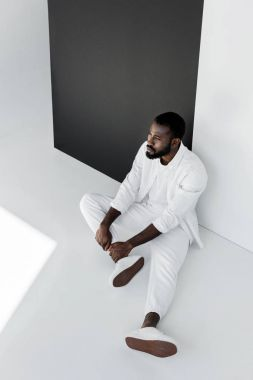 high angle view of handsome stylish african american man sitting on floor in white clothes