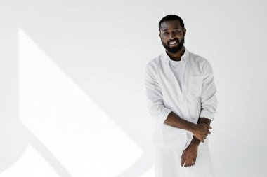 smiling stylish african american man in white clothes looking at camera on white