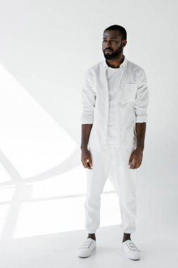 handsome stylish african american man standing in white clothes on white