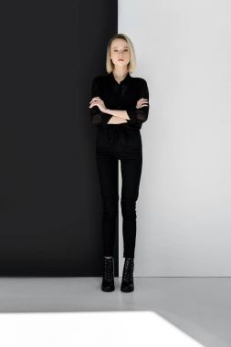 attractive stylish blonde woman in black clothes standing with crossed arms near black and white wall