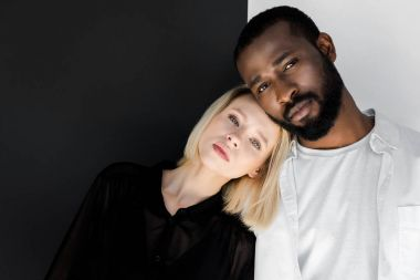 african american boyfriend and blonde girlfriend hugging and looking at camera