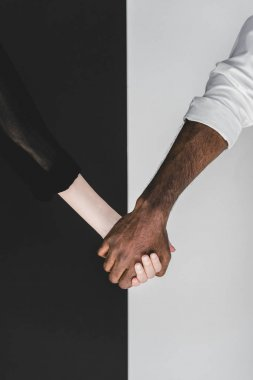 cropped image of multicultural couple holding hands, yin yang concept