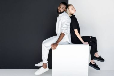 african american boyfriend and blonde girlfriend sitting back to back on white cube
