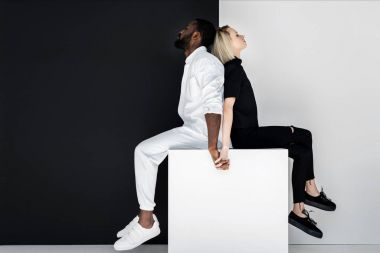 multicultural couple holding hands on white cube, yin yang concept