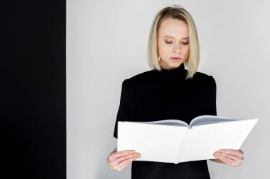 attractive stylish blonde woman in black clothes reading white book