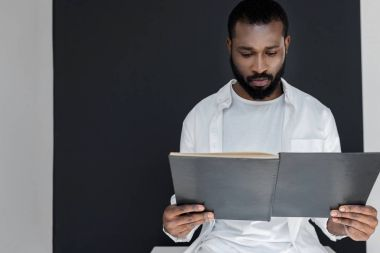 handsome stylish african american man in white clothes reading black book