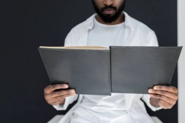 cropped image of stylish african american man in white clothes reading black book