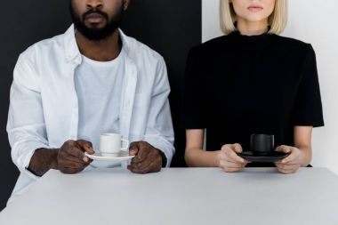 cropped image of african american boyfriend and blonde girlfriend holding cups of coffee