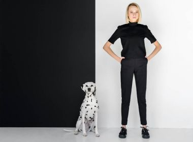 beautiful stylish blonde woman in black clothes standing near black and white wall with dalmatian dog