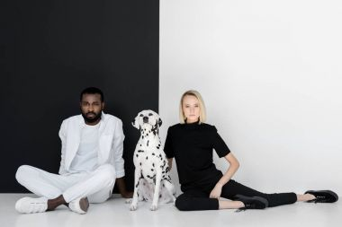 multicultural couple sitting near black and white wall with dalmatian dog