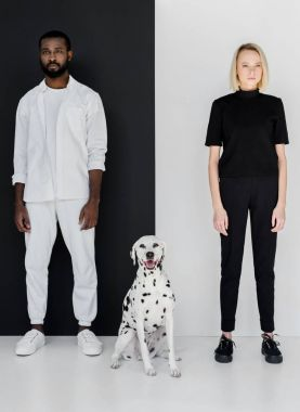 african american boyfriend and girlfriend standing with dalmatian dog near black and white wall
