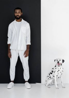 handsome stylish african american man in white clothes and dalmatian dog standing near black and white wall