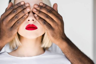 cropped image of african american boyfriend closing eyes of blonde girlfriend