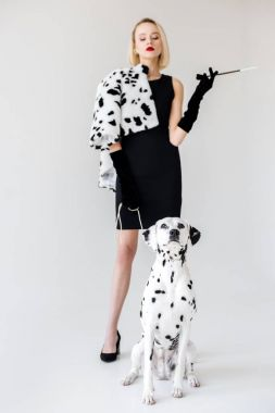 attractive stylish blonde woman in black dress looking at dalmatian dog on white