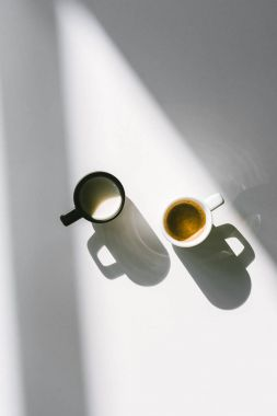 top view of black and white cups of milk and coffee on white surface
