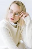portrét krásné stylové blondýnka v bílých šatech dotýká brýle izolované na bílém