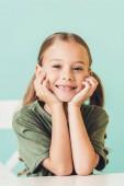 portrét rozkošné malé dítě sedí u stolu a usmívá se na kameru