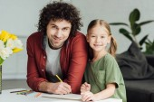 Fotografie happy father and daughter drawing together and smiling at camera at home