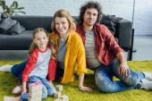 Fényképek boldog családi ül a szőnyegen, és mosolyogva kamera fadarabot otthon játék közben