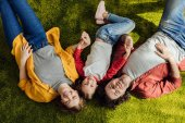 Fotografie top view of happy parents with adorable little daughter lying together and smiling at camera