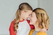 Glückliche Mutter und Tochter umarmen und lächeln zu Hause