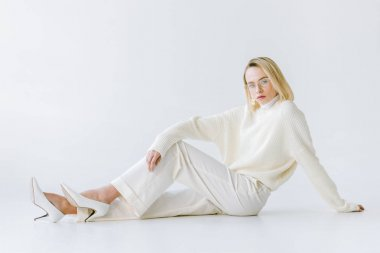 attractive stylish blonde woman in white clothes sitting on white floor