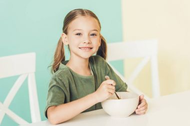 cute little child having breakfast and smiling at camera