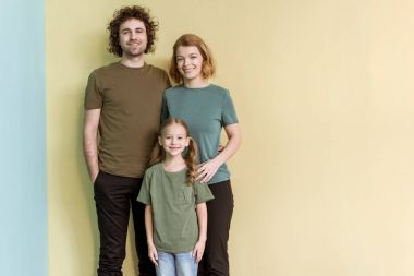 happy family with one child standing together and smiling at camera