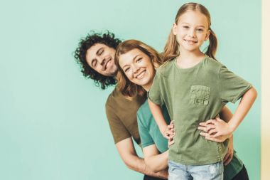 Happy parents with cute little daughter wearing t-shirts and smiling at camera stock vector