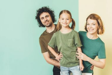 happy family with one child wearing t-shirts and smiling at camera