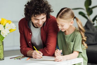 happy father and little daughter drawing with colored pencils at home