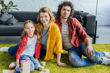 happy family sitting on carpet and smiling at camera while playing with wooden blocks at home