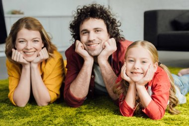 happy family with one child lying together and smiling at camera