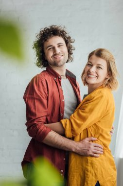 selective focus of happy young couple hugging and smiling at camera at home
