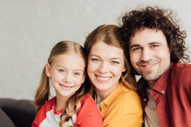 portrait of beautiful happy young family smiling at camera