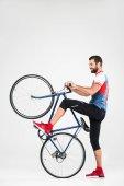 Fotografie pohledný sportovec pózuje s kolo, izolované na bílém