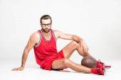 basketbalista v červené oblečení a brýle sedí s míčem, izolované na bílém