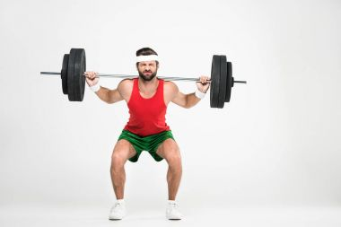 sportsman in retro sportswear squating with barbell, isolated on white