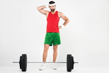 thoughtful sportsman standing near barbell, isolated on white