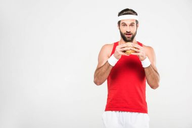 excited sportsman eating hamburger, isolated on white