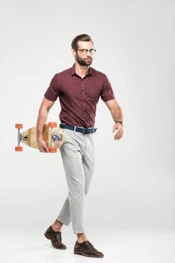 stylish elegant skater walking with longboard, isolated on grey