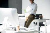 vista ravvicinata del computer desktop e tazza di carta, uomo che si appoggia al tavolo dietro